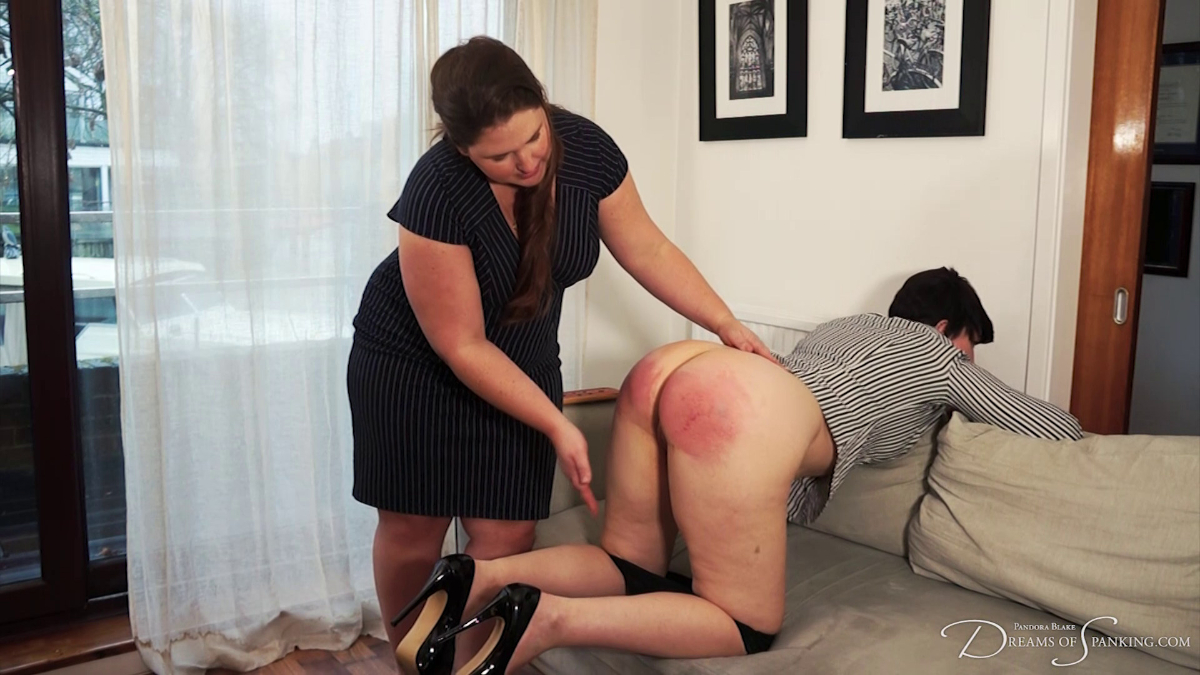 Pandora Blake bent over the sofa as Kelley May gives her an intense paddling